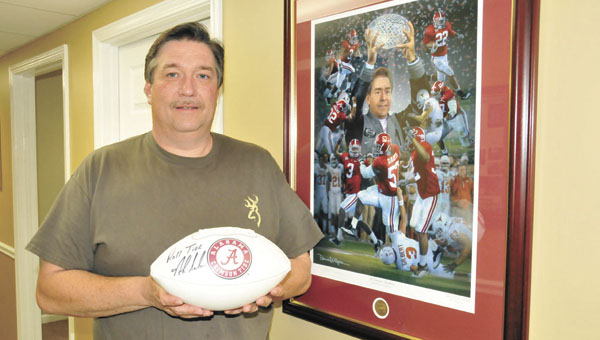Alan Williamson holds the autographed football for auction. | Andrew Garner/Star-News