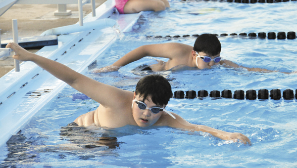 Dong Won Kim and Dong Goan Kim swim Tuesday night at during the 10-and-under team's practice at Cooper Pool. |                                          Andrew Garner/Star-News