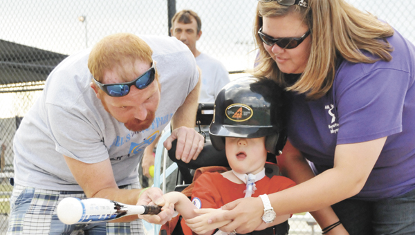 Derek and Emily Mitchell help their son, Baker, hit the ball during Tuesday night's contest at the Covington County Mirale League game.                  Andrew Garner/Star-News