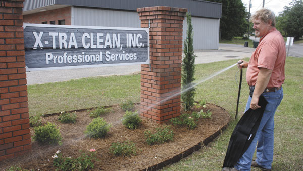 Bobby Taylor waters the flowers outside X-tra Clean Inc., on Thursday.