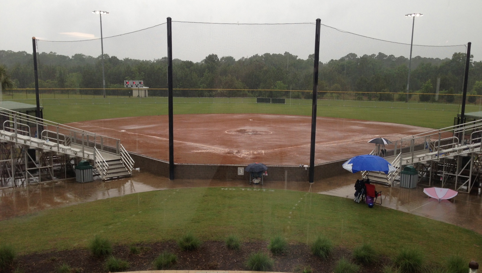 Puddles of water build up on Field No. 3, where Pleasant Home and Kinston were playing this morning before lightning and  rain delayed the game. | Andrew Garner/Star-News