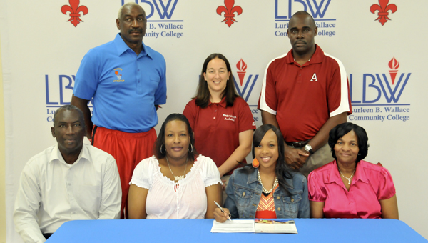 Tyleshia Malcolm (front row, second from right) signed a basketball scholarship at LBWCC Thursday morning. She is flanked by her mother, Pamela Curry, Carolyn Curry and Joe Curry. LBWCC coach Ricky Knight (back row, far left), Andalusia girls basketball coach Teresa Herring and AHS principal Dr. Daniel Shakespeare were also in attendance at the signing. | Andrew Garner/Star-News