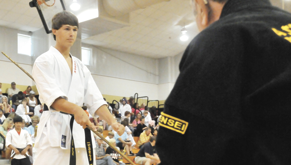 Allen Butler (left) won the youth black belt forms and weapons grand championship. |       Andrew Garner/Star-News