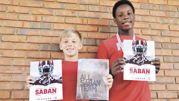 Gage Messick (left) and Ke'Shun Townsend pose for a photo with their Nick Saban Football Camp programs and stat sheets on how they did on the gridiron. | Andrew Garner/Star-News