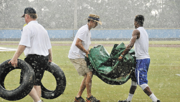 Field crew drag out the home plate tarp Saturday. The 15-year-old Alabama Babe Ruth State Tournament had endured four rain delays. | Andrew Garner/Star-News