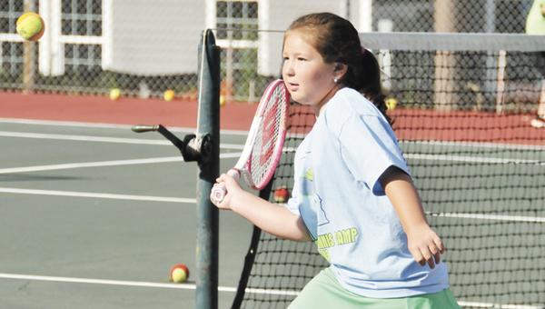 Paige Garvin returns a serve during the Andalusia Tennis Association's summer tennis program Thursday morning. | Andrew Garner/Star-News