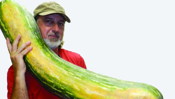 Neal Dansby holds the 56-pound squash grown by his father, Leon.
