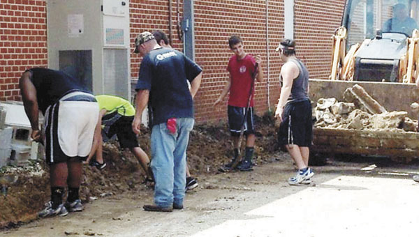 Volunteers work on the side of the building adjacent to the stadium Thursday. | Courtesy photo