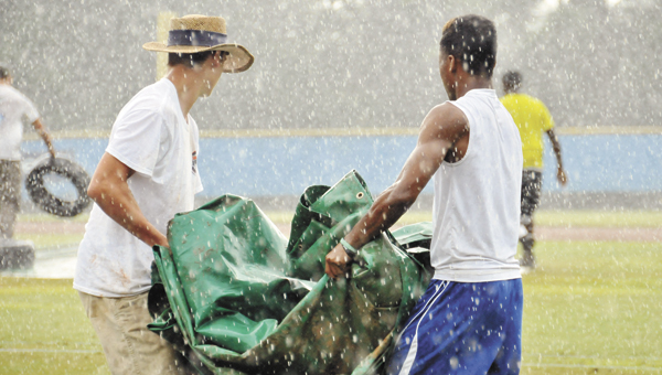 Field crew workers bring out a tarp to cover home plate at LBWCC during a rain delay at the Babe Ruth 13-to-15-year-old state tournament.   Andrew Garner/Star-News