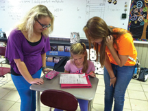 Peyton Harris and Menna Williamson, Straughn High School JAG students, work with Alora Morgan after school Thursday.