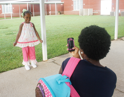 Tawona Grandison takes a photo of her daughter, Trinitie Monday at AES