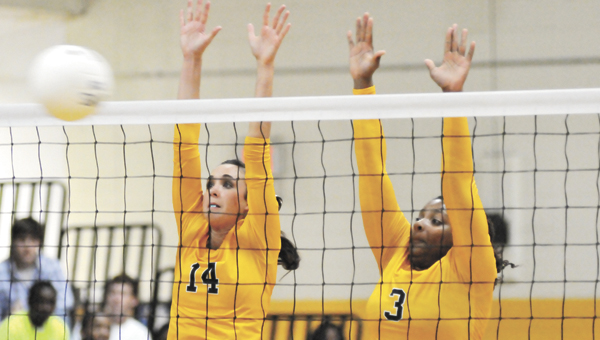Opp's Laiken Free (14) and Olivia Bradley (3) block a kill Thursday night during the Lady Bobcats' 3-0 area win over Straughn. The Lady Bobcats also clinched a berth to host the area tournament. |        Andrew Garner/Star-News