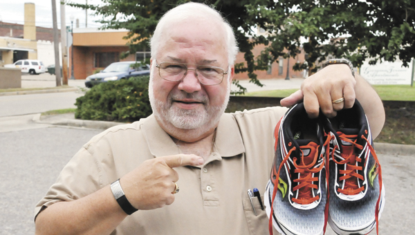 Tim Trent holds up the shoes he's going to wear in tomorrow's 5K. |                                  Andrew Garner/Star-News
