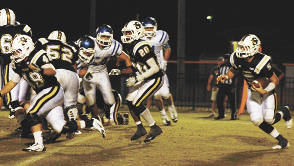 Straughn's Rollin Kinsaul (5) runs the ball as the offensive line and other players give him some room Friday night. | Blake Bell/Star-News