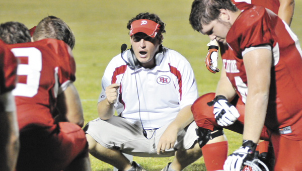 Pleasant Home defensive coordinator Lamar Gibson talks to his players during an injury timeout at a recent game. | File photo