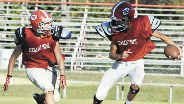 Pleasant Home quarterback Garrett Barton (right) gets rushed by a fellow teammate Wednesday night at practice.   Andrew Garner/Star-News
