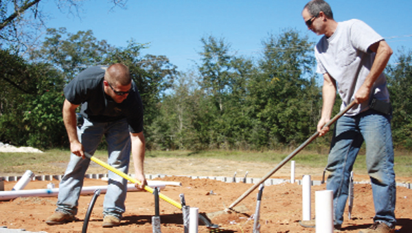 Derek Hester and Steve Pierce of Pierce Electrical and Plumbing work at the Habitat site Wednesday.