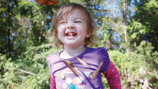 Allyn Hudson, 2, enjoys the cool weather and the abundance of leaves Wednesday afternoon.