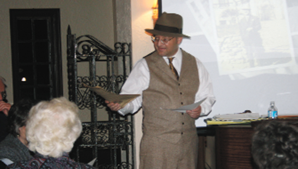 Covington Historical Society President John Scherf dons a fedora during Thursday's meeting as he tells members of the life of his great-grandfather, John. G. Scherf.