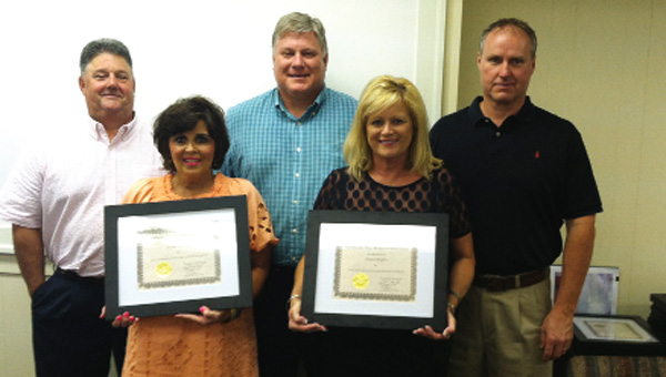 Among the retirees recognized Monday night were Vickie Ptomey and Jenny Rogers. They are shown here with their spouses and Superintendent Ted Watson, from left, Joe Ptomey, Mrs. Ptomey, Watson, Mrs. Rogers, Paul Rogers.