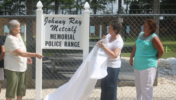 The Johnny Ray Metcalf Memorial Police Range was officially dedicated Tuesday. Pictured are, from left, his sister, Mary Anderson; wife, Pauline Metcalf; and daughter, Michelle Jones, unveiling the new sign.