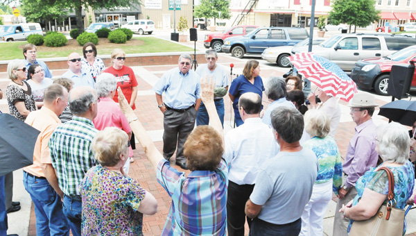 "The Rev. Leroy Cole and a group of Covington County residents sing ""Victory in Jesus"" Thursday afternoon during the National Day of Prayer on the court square. 
