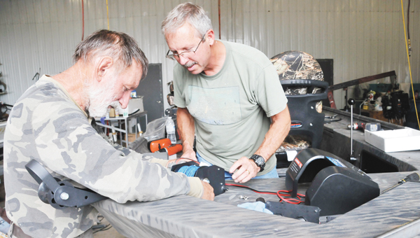 Rigging technicians Mike Peterson (right) and Warren Paulsen work on a vessel at Andalusia Marine Thursday afternoon. Boating season will be in full swing soon, so don't forget to wear life jackets. | Andrew Garner/Star-News