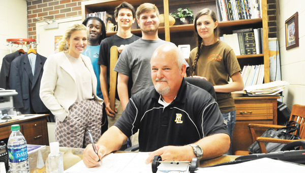 0520 Odom with students – Red Level High School Principal Johny Odom sits at his desk with a group of students. The students are form left, Morgan Odom, Chavis Crittenden, Andrew Owens, Trenton Mancill and Taylor Liles. Odom is retiring at the end of the school year. | Andrew Garner/Star-News