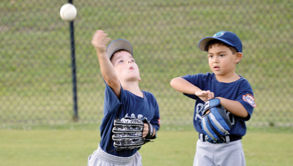 Levi Carrol (left) throws from the outfield during rec-league action Tuesday night. Last night was the last of the regular season for rec sports. | Josh Dutton/Star-News
