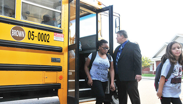 A few cheers and tears were shed Monday morning for the first day of school at Andalusia Elementary. Along with Andalusia, Opp City Schools marked their first day back in the classroom yesterday. Top: Andalusia Elementary students file out of the bus as Assistant Prinicipal Rob Mixson extends a warm welcome back. | Andrew Garner/Star-News