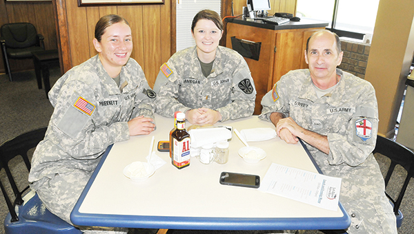 Current military personnel and 2nd Lts. Stephanie Preekett and Erin Hannigan, along with D.A.C. (Department of the Army Civilian) Phil Sweet, pose for a photo at the airport café. | Andrew Garner/Star-News