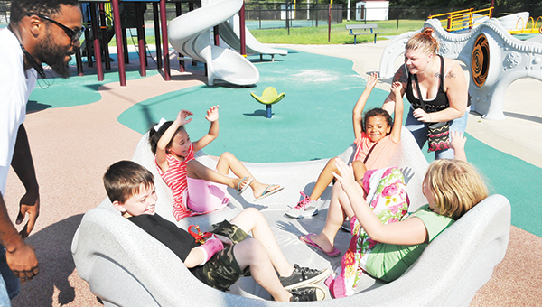 Wendy Cauley (right) and Samuel Johnson spin a park ride as Diamond Stallworth, Alia Johnson, Gracie Farmer and Jacob McClellan around and around Thursday afternoon. | Andrew Garner/Star-News
