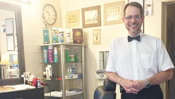 Hughie Atkison stands in his barbershop.