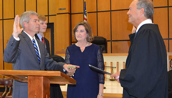 Former District Judge Trippy McGuire, right, administers the oath of office to Circuit Judge Ben Bowden. His wife, Angie, is holding the Bible, and his son, Sim, holds his black judicial robe.