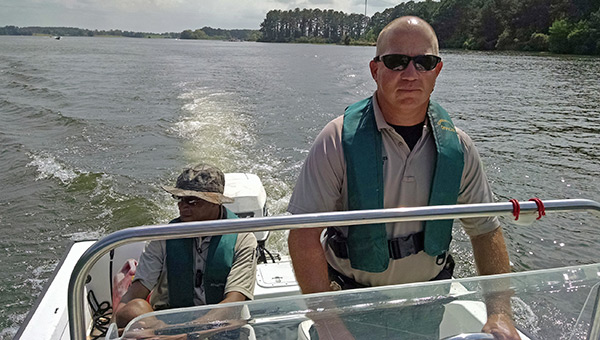 PHOTOS: (ADCNR) Conservation Enforcement Officer Vance Wood mans the helm of one of Alabama Wildlife and Freshwater Fisheries (WFF) Division's boats as fellow officer Bill Freeman aids in the patrol of the inland waterways. Hunting and fishing license checks are just one aspect of a enforcement officer's many duties.