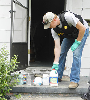 DTF Agent Josh Hudson places muriatic acid, along with other ingredients used in a meth lab found at 302 College St. in Andalusia Tuesday, on the front porch.