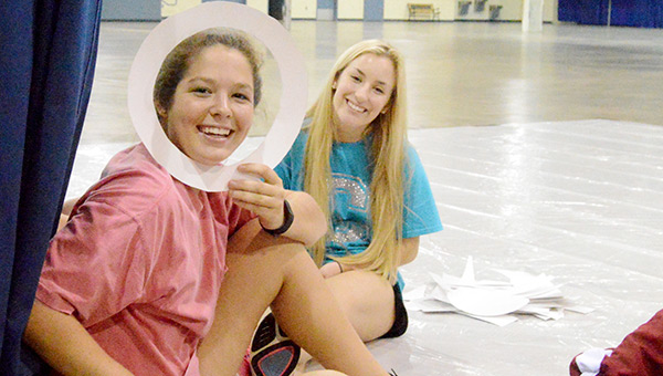 AHS students Kat Finley and Catherine Weed have some fun while preparing decorations for their homecoming float Monday night at the Kiwanis Center.