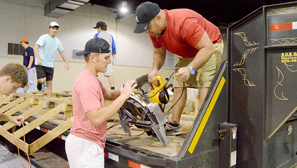 Lane and Steven Prevett get the equipment ready to start working on floats Monday night at the Kiwanis Center for Andalusia High School's homecoming week.