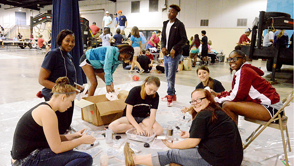 AHS seniors Heather Hamm, Brittany Williamson, Janikqua Lane, Courtney Bulger, Faith Brundidge, Elizabeth Cravey, Zareyah Hines and Kendrick Brown work on decorations for the senior class homecoming float at the Kiwanis Center on Monday night.
